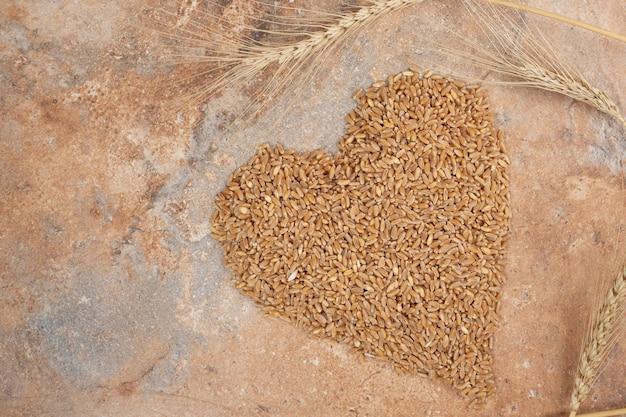Bouquet d'orge formé comme un coeur sur un espace orange.