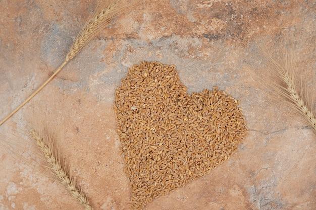Bouquet d'orge formé comme coeur sur fond orange