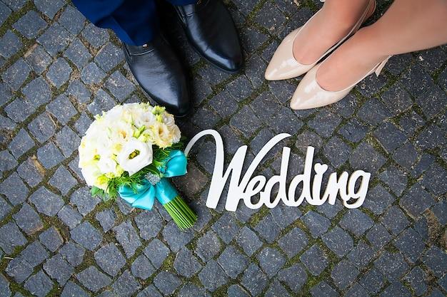 Bouquet et un panneau en bois au mariage est le couple de pieds