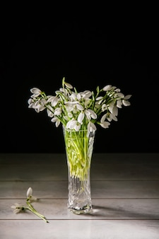 Bouquet de perce-neige blanc galanthus nivalis dans un bocal en verre sur des tons foncés sur une surface en bois.