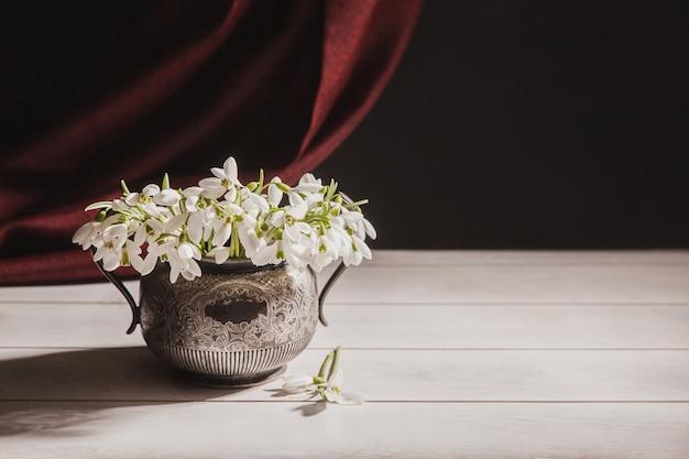 Bouquet de perce-neige blanc galanthus nivalis dans un pot rétro vintage sur un des tons sombres avec tissu rouge sur la surface.