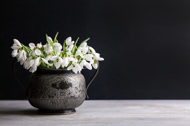 Bouquet de perce-neige blanc galanthus nivalis en pot rétro vintage sur une surface sombre avec espace de copie.
