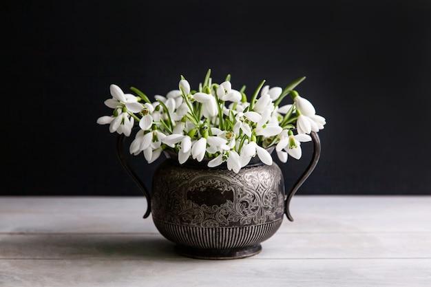 Bouquet de perce-neige blanc galanthus nivalis en pot rétro vintage sur surface sombre.