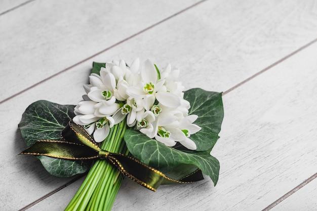 Bouquet de perce-neige blanc galanthus nivalis sur une surface en bois blanche avec un espace pour le texte. vue de dessus, pose à plat.