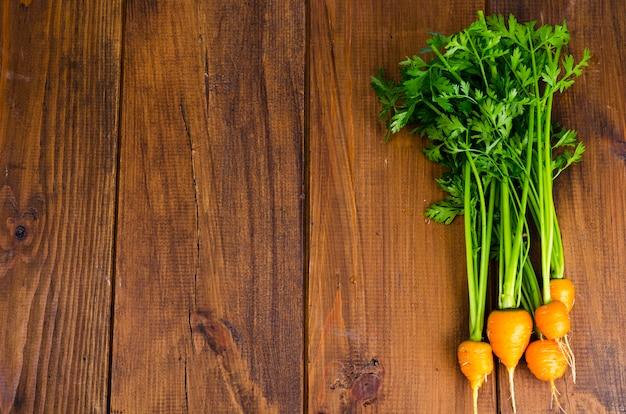 Bouquet de petites carottes rondes (carottes héritage parisien) sur fond en bois.