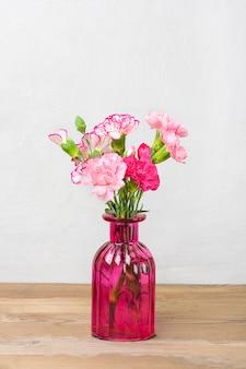 Bouquet de petits œillets roses colorés dans un vase sur une surface en bois et un mur gris