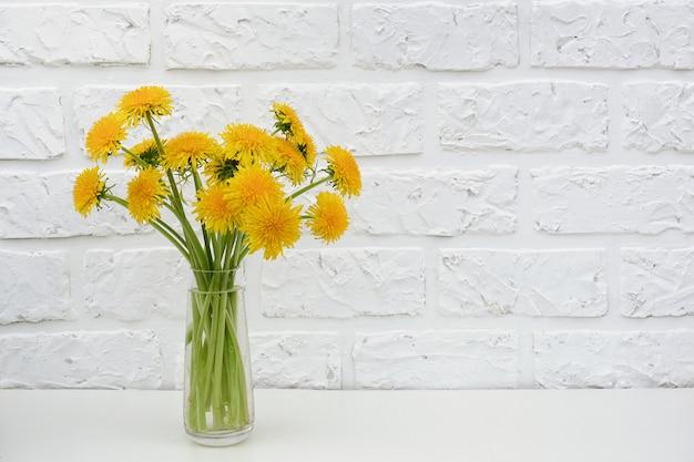 Bouquet de pissenlit jaune dans un vase sur le mur de briques blanches du fond de la table