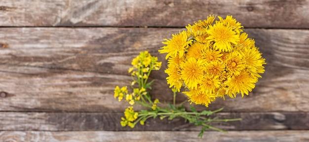 Bouquet de pissenlits jaunes sur fond de bois vue de dessus