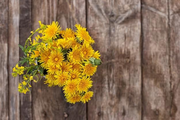Bouquet de pissenlits jaunes sur fond de bois