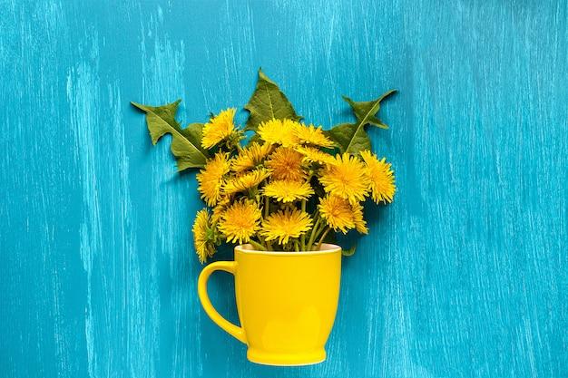 Bouquet de pissenlits taraxacum fleurs dans une tasse jaune