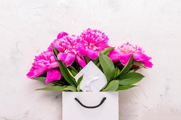 Bouquet de pivoine dans un sac blanc et une boîte-cadeau sur fond blanc.