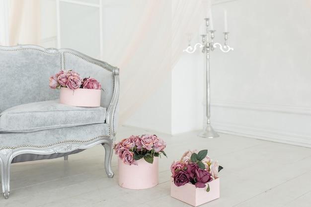 Bouquet de pivoine pourpre et de belle fleur beige au sol dans la boîte rose dans une pièce blanche et lumineuse