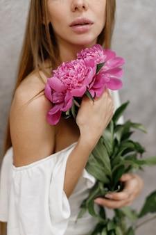 Un bouquet de pivoines dans les mains d'un gros plan de femme
