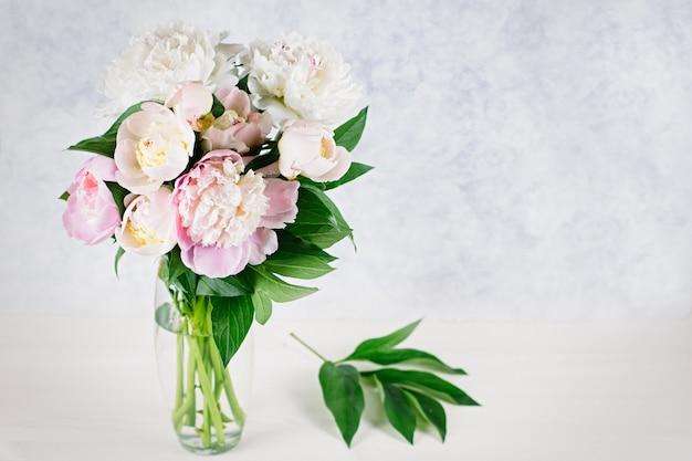Bouquet de pivoines dans un vase gros plan sur mur pastel