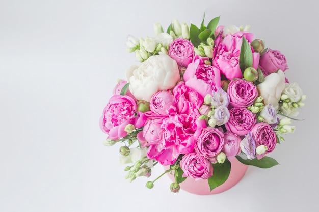 Bouquet de pivoines, eustoma, spray dans une boîte rose