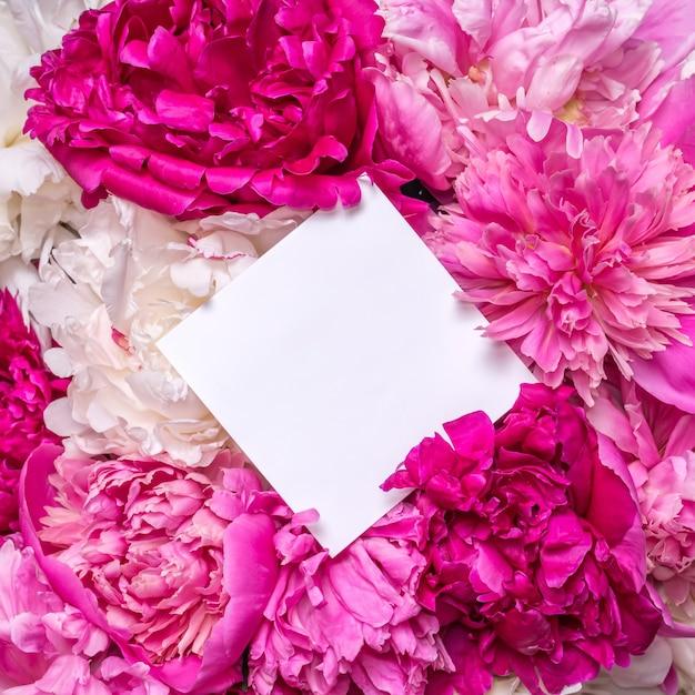 Un bouquet de pivoines et une note à l'intérieur. fleurs violettes de printemps.