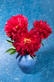 Bouquet de pivoines rouges dans un vase en céramique bleu sur fond texturé bleu. carte de voeux festive lumineuse. fleurs pour mère ou femme dans sa journée de vacances. orientation verticale. mise au point sélective.