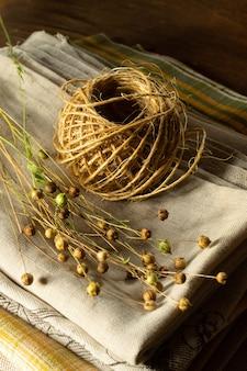 Bouquet de plantes de lin séchées et un écheveau de corde sur un textile en lin