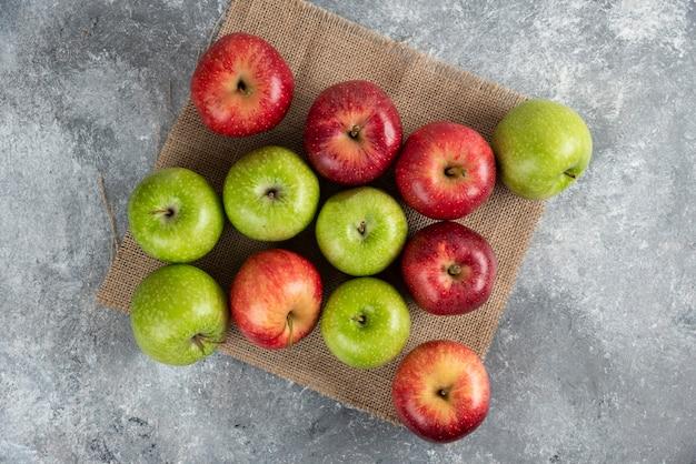 Bouquet de pommes vertes et rouges fraîches placées sur de la toile de jute.