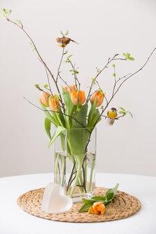 Bouquet de printemps frais de tulipes oranges et de feuilles vertes et de petits oiseaux dans un joli vase en verre cristal