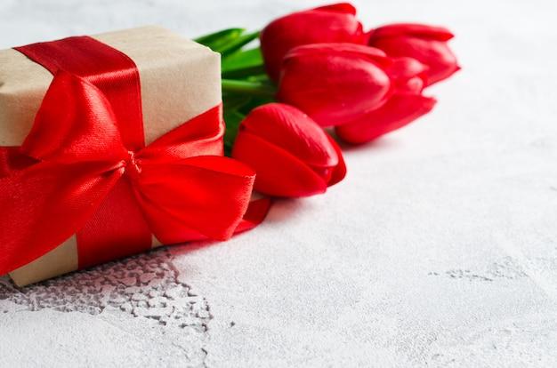 Bouquet de printemps de tulipes rouges et une boîte cadeau.