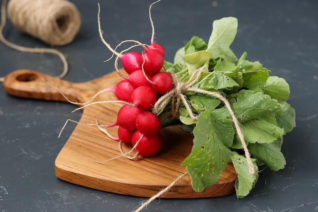 Bouquet de radis est situé sur une planche de bois sur un fond sombre