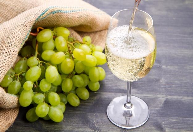 Bouquet de raisins verts et vin sur fond en bois