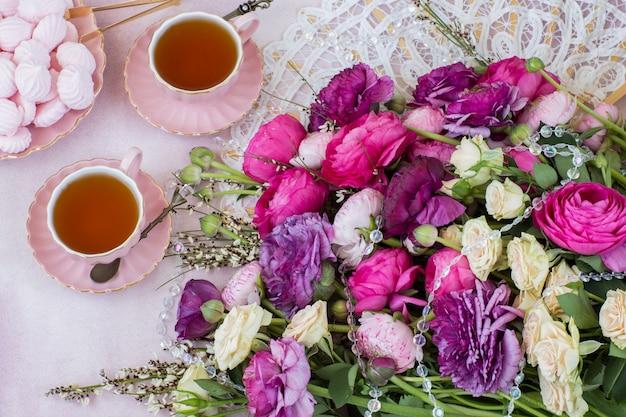 Un bouquet de renoncule, deux tasses de thé et de meringue