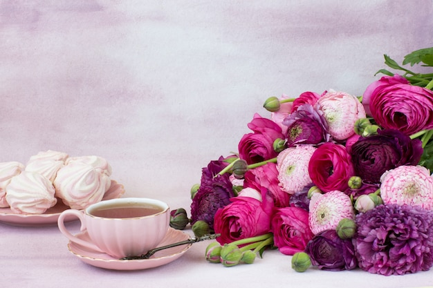 Un bouquet de renoncule, une tasse de thé et des guimauves dans une assiette