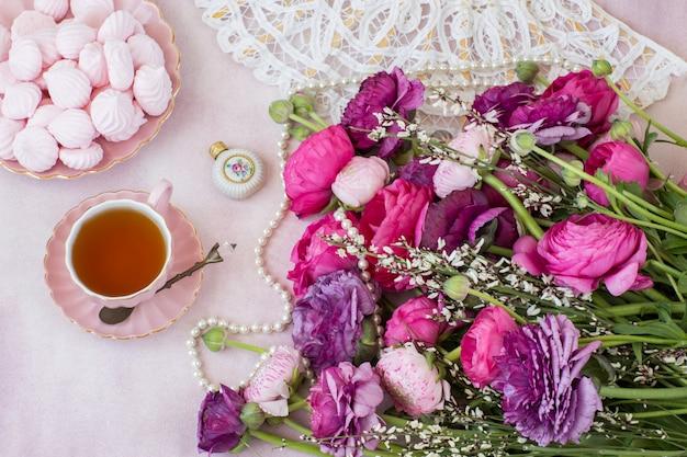 Un bouquet de renoncule, une tasse de thé, de la meringue, un éventail et une bouteille de parfum