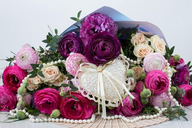 Un bouquet de renoncules, de roses, de perles et un coeur de dentelle
