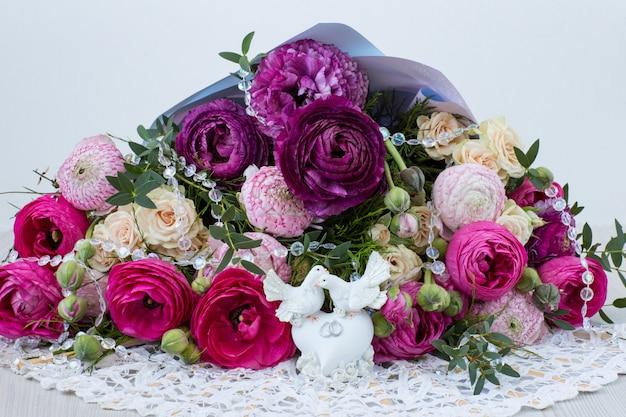 Un bouquet de renoncules et de roses sont deux colombes blanches avec des alliances