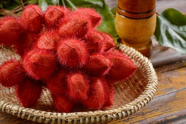 Bouquet de rocou au tamis de paille sur table en bois.