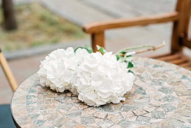 Bouquet romantique solitaire de fleurs d'hortensia blanc sur une table en pierre. mise au point sélective douce.