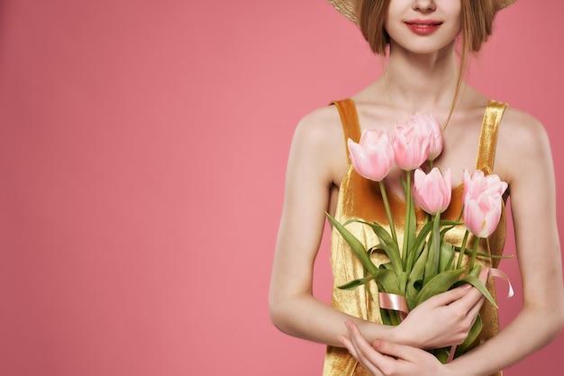 Bouquet rose des fleurs dans les mains d'une décoration de luxe de robe d'or de femme
