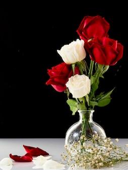 Bouquet rose rouge et blanc dans un vase en verre sur fond noir
