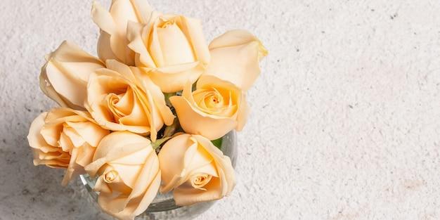 Bouquet de roses beiges fraîches dans un vase. le concept festif pour les mariages, les anniversaires, le 8 mars, la fête des mères ou la saint-valentin. carte de voeux, fond clair, bannière