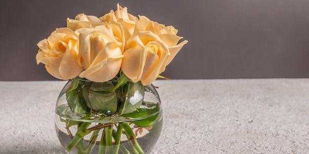 Bouquet de roses beiges fraîches dans un vase. le concept festif pour les mariages, les anniversaires, le 8 mars, la fête des mères ou la saint-valentin. carte de voeux, fond sombre