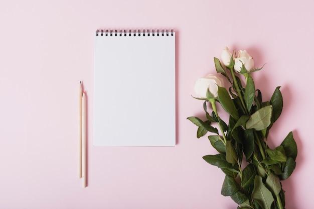 Bouquet de roses blanches avec bloc-notes en spirale et crayons de couleur sur fond rose