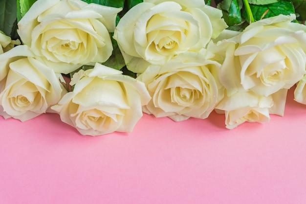 Bouquet de roses blanches en fleurs sur fond rose pastel. cadre floral romantique. espace copie