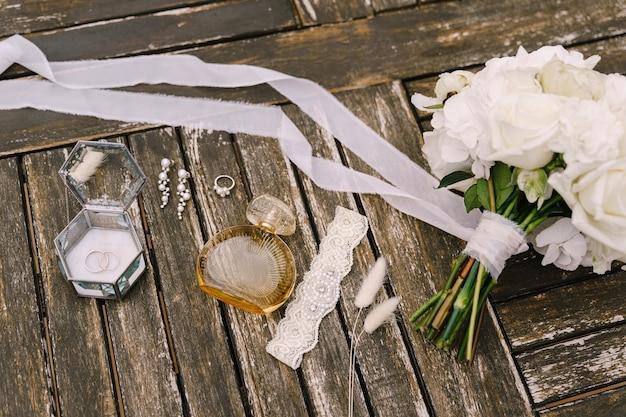 Un bouquet de roses blanches avec un long ruban en développement une jarretière ajourée une bouteille de parfum une bague