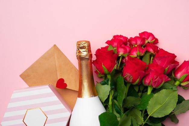 Bouquet de roses, bouteille de champagne et coffret cadeau vue de dessus plat