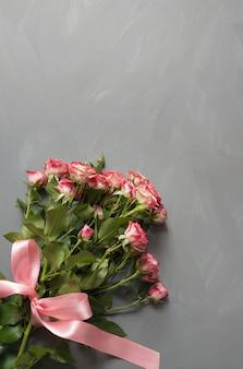 Bouquet de roses de brousse roses avec noeud rose sur gris