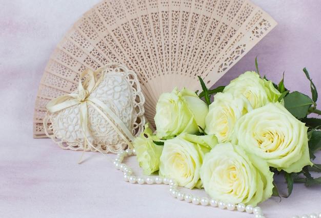 Bouquet de roses claires, coeur de dentelle, éventail et perles sur fond rose