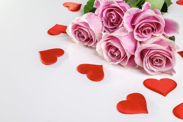 Bouquet de roses et de coeurs sur fond blanc. carte ou bannière de la saint-valentin.