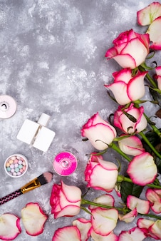 Bouquet de roses avec des cosmétiques au parfum sur un fond gris avec espace de copie