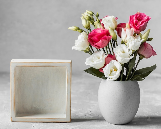 Bouquet de roses à côté d'un cadre vide