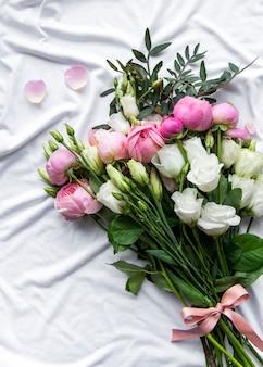 Bouquet de roses de couleur rose sur textile blanc froissé. vue de dessus, mise à plat.