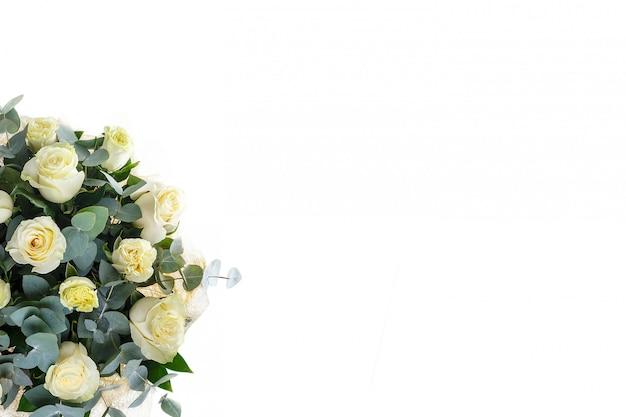 Bouquet de roses et d'eucalyptus sur un mur blanc