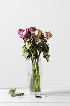 Bouquet de roses fanées dans un vase en verre sur un mur blanc.